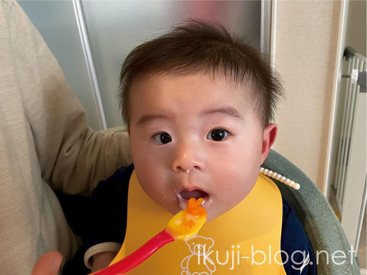 離乳食のにんじんを見て口をあける赤ちゃん