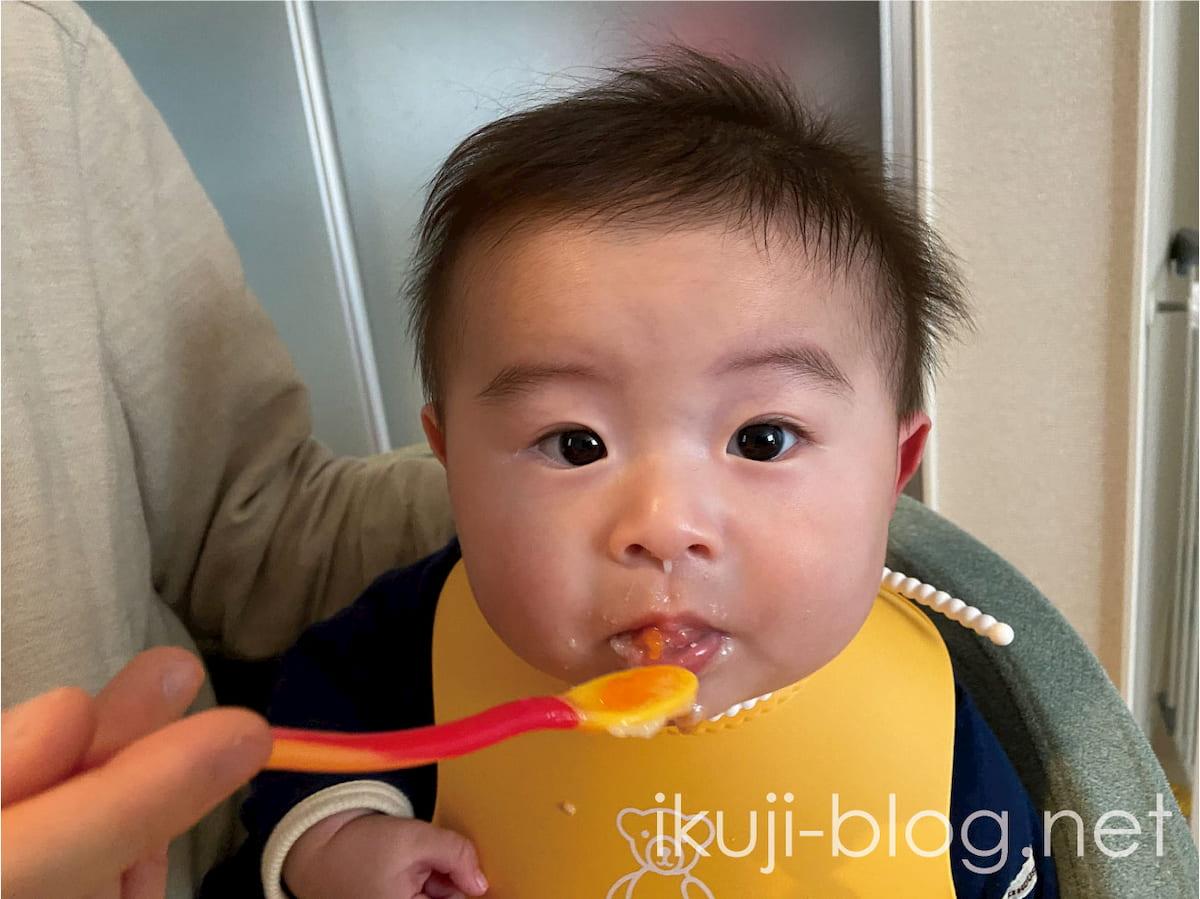 離乳食のにんじんを口から吐き出す赤ちゃん
