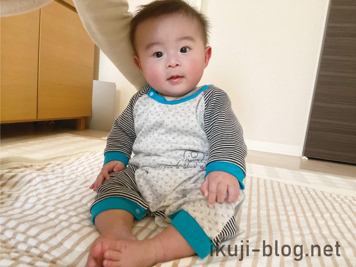 大人に支えられながら座る赤ちゃん